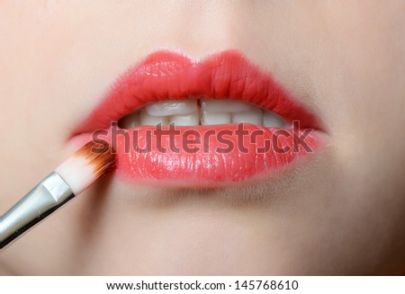 Female lips close up with lipstick brush