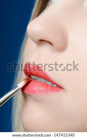 Female lips close up with lipstick brush - stock photo