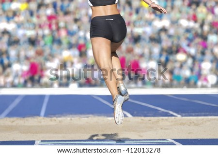 Female long jumpers jump into the sand box. In the background there can be seen fully occupied ranks with spectators. - stock photo