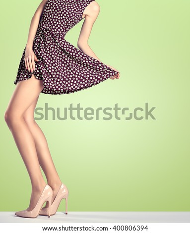 Female long legs in fashion skirt and high heels. Female sexy legs, stylish purple dress and summer glamour heels on legs. Unusual creative elegant sexy girl pose. Fashion trendy female outfit, shoes - stock photo