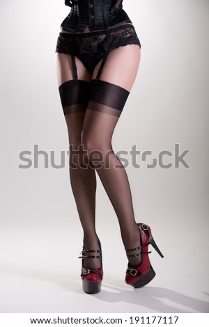 Female long legs in vintage nylon stockings and high heels, studio shot on white background