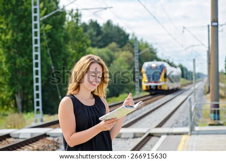 Female looking to the map on the platform of railway station. Train is coming. - stock photo