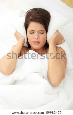 Female lying on bed and closing her ears with pillow