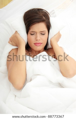 Female lying on bed and closing her ears with pillow - stock photo