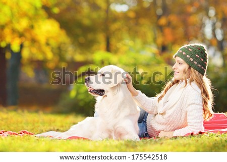 Female lying on grass with her labrador retriever dog in a park - stock photo