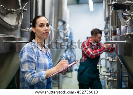 Female maintenance worker testing brewery machine at brewery