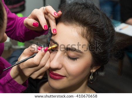 Female make up artist working on model in salon