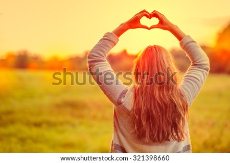 female making symbol for loving the season - stock photo