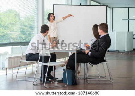 Female manager delivering presentation to a team of coworkers - stock photo