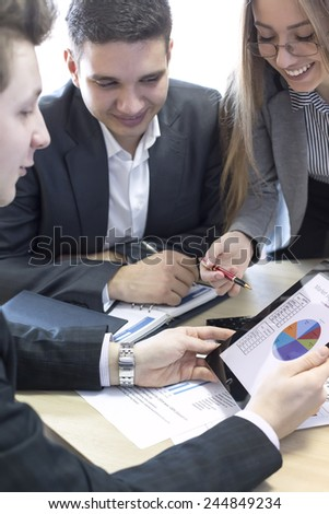 Female manager explains corporate data to her associate. Group of business people discuss the data using tablet PC and paper charts and presentations. - stock photo