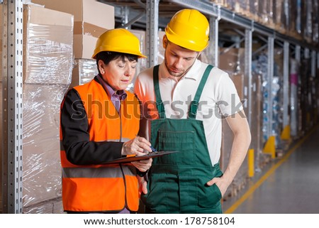 Female manager giving worker advice in warehouse - stock photo