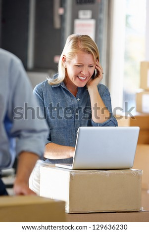 Female Manager Using Mobile Phone In Distribution Warehouse - stock photo