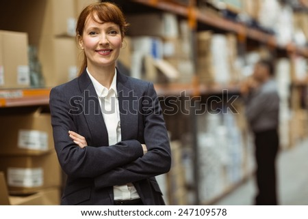 Female manager with arms crossed in a large warehouse - stock photo