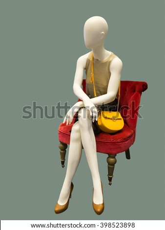 Female mannequin sitting on red armchair, against green background. No brand names or copyright objects. - stock photo