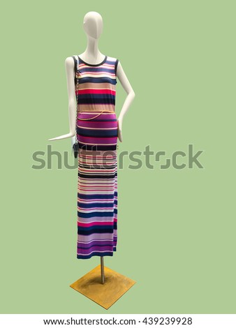 Female mannequin wearing stylish knitted dress isolated on green background. No brand names or copyright objects. - stock photo