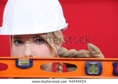 Female manual worker with spirit level - stock photo