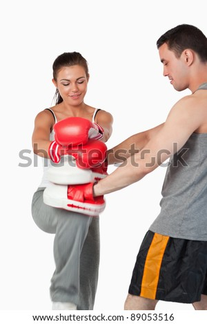 Female martial arts fighter practicing her knee technique against a white background - stock photo
