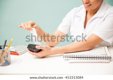 Female masseuse printing a payment receipt and smiling at a beauty spa. Closeup with some copy space - stock photo