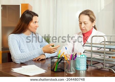 Female mature doctor examining teenage girl in hospital - stock photo