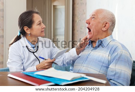 Female mature doctor looks the throat of senior patient in clinic - stock photo