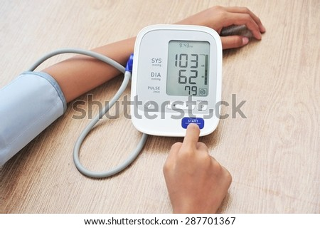 Female measures her blood pressure.