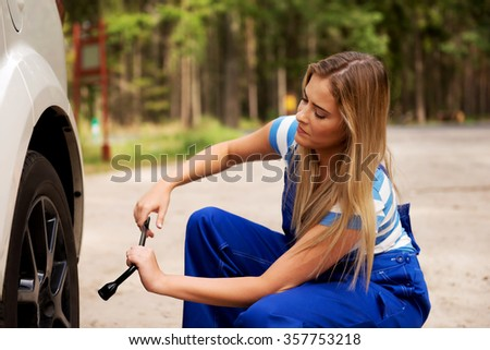 Female mechanic changing tire with wheel wrench. - stock photo