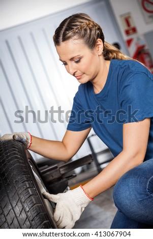 Female Mechanic Examining Car Tire - stock photo