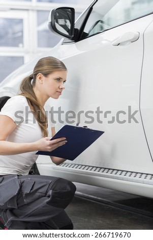 Female mechanic holding clipboard while examining car body at repair shop