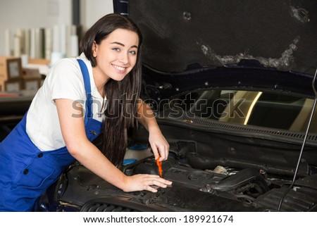 Female mechanic in garage or workshop repairing car - stock photo