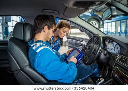 Female mechanic looking at male colleague using digital tablet in car at garage - stock photo