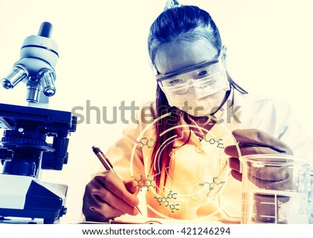 female medical or scientific researcher or woman doctor looking at a test tube of clear solution in a laboratory with her microscope beside her;with chemical equations - stock photo