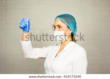 Female medical or scientific researcher or woman doctor looking at a test tube of clear solution in a laboratory. - stock photo