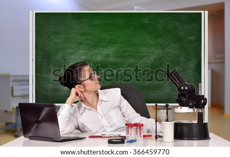 female medical or scientific researcher sitting in laboratory with blank blackboard - stock photo