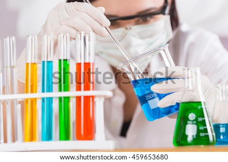 Female medical or scientific researcher using test tube on laboratory.