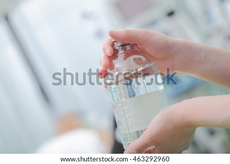 Female medical worker holding bottle of drug.