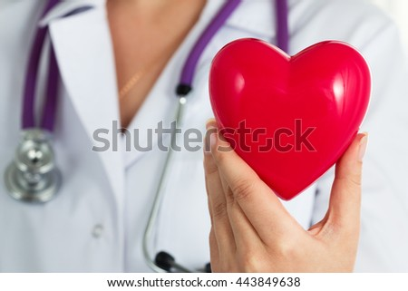 Female medicine doctor hold in hands red toy heart closeup. Cardio therapeutist, physician make cardiac physical, heart rate measure or arrhythmia concept - stock photo