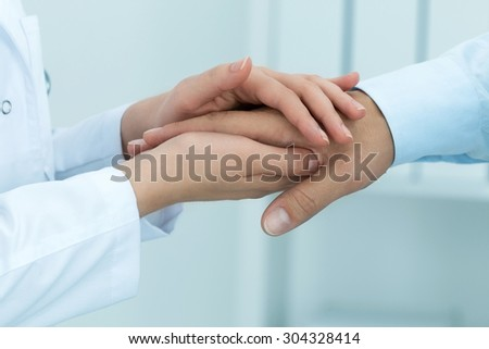 Female medicine doctor reassuring her patient. Hands close-up. Healthcare and medical concept. - stock photo