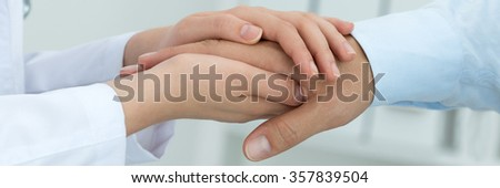 Female medicine doctor reassuring her patient. Hands close-up. Healthcare and medical concept. Letter box format - stock photo