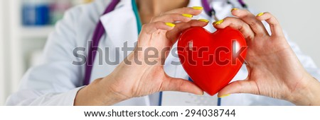 Female medicine doctor's hands holding red toy heart in front of her chest closeup. Letterbox view. Medical help, prophylaxis or insurance concept. Cardiology care,health, protection and prevention - stock photo