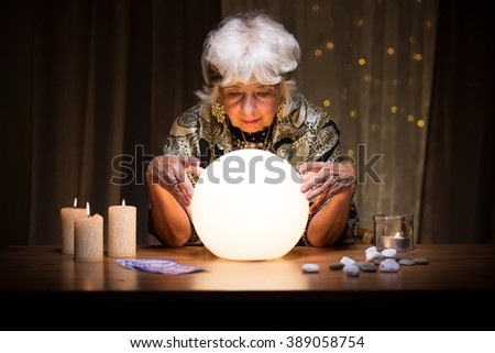 Female medium sitting with magical crystal ball - stock photo