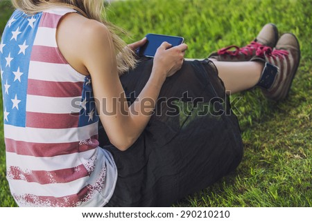 Female model against a green lawn in a t-shirt with an American flag and a phone - stock photo