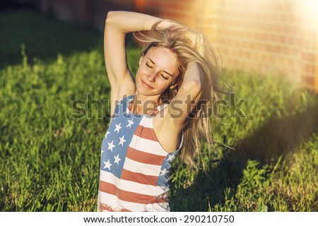Female model against a green lawn in a t-shirt with the American flag - stock photo