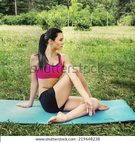 female model doing yoga exercise outdoor in the city park. retro filter photo effect.  - stock photo