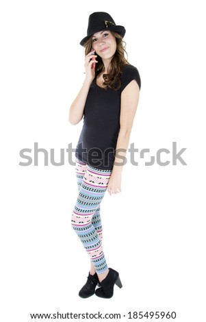 Female model in colorful leggings, black top, black sun hat, black high heels talking on her cell phone