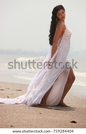 Female model in long white dress at the beach during sunny afternoon