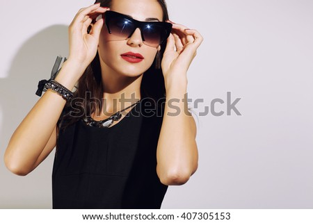 Female model in sunglasses and black dress luxury style
