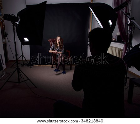 Female model posing at studio in the light flashes. Photographer working with a woman in a photo studio. Young beautiful woman posing during photo shooting. - stock photo