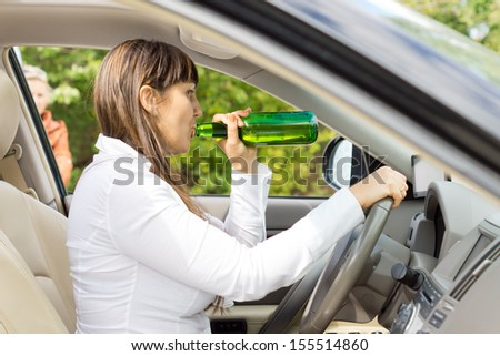Female motorist drinking and driving while being watched from outside by a young boy - stock photo