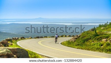 Female mountain bike cyclist riding downhill along Cadillac Mountain road in Acadia National Park, a clear summer day with panoramic view of Acadia National Park (Maine, USA) landscape with lakes. - stock photo