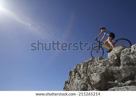 Female mountain biker sitting on bicycle at edge of rock in sunlight, low angle view (lens flare)